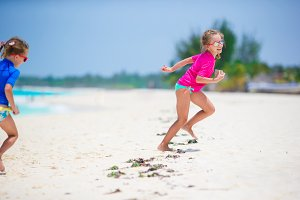 Little girls having fun at tropical beach playing together on the beach