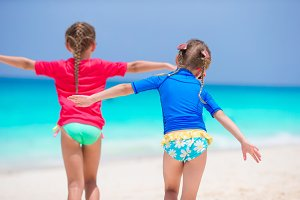 Little girls have fun at tropical beach playing together