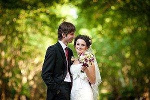 Curly bride smiles behind a groom