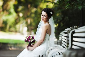 Subtle bride sits on the white bench