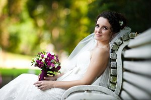 Curly bride holds a violet bouquet