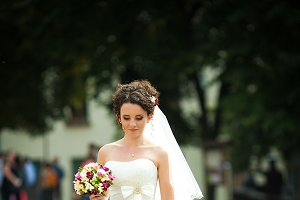 Tiny brunette bride on the pavement