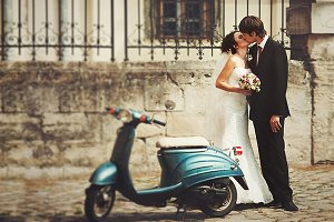 Couple kisses behind a blue scooter