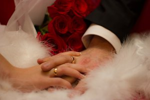 Hands of man and woman with wedding ring - fur and roses