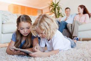 Siblings using tablet on the living room floor