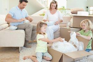 Family unpacking cardboard box
