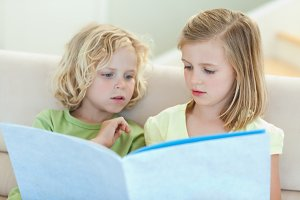 Siblings reading magazine on the couch