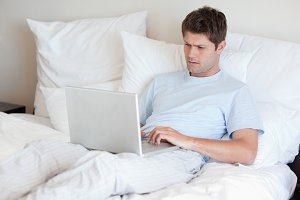 Man lying in bed with laptop