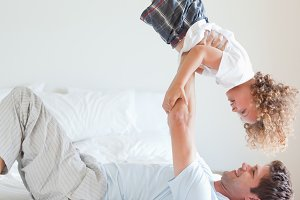Side view of father lifting child on bed