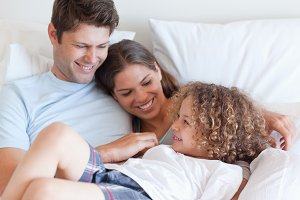 Happy family relaxing on a bed