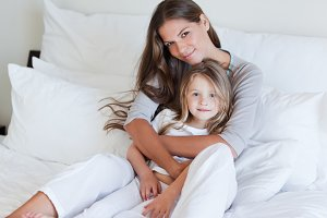Young mother and her daughter posing on a bed