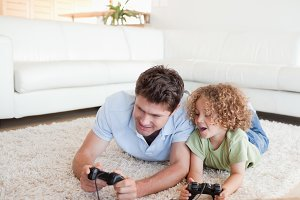 Cheerful boy and his father playing video games