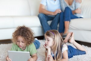 Children using a tablet computer while their parents are watching