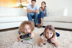 Cute children playing video games while their parents are watching