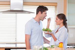 Happy couple tasting a salad
