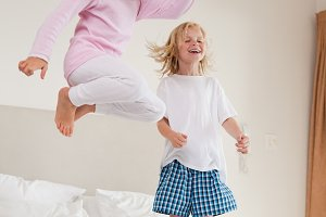 Portrait of playful siblings jumping
