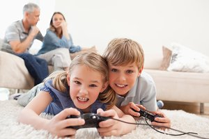 Cheerful children playing video games with their parents on the background