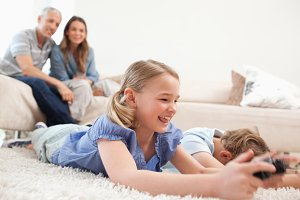 Children playing video games with their parents on the background