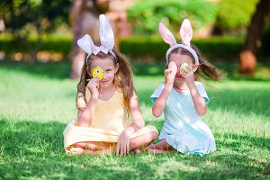 Two little girls wearing bunny ears on Easter eve outdoors