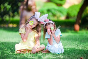 Little cute girls with bunny ears have fun with eggs on Easter holiday