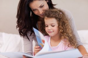 Mother reading a book with her daughter