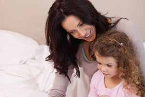 Mother reading bedtime story for her daughter