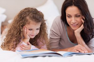 Little girl reading bedtime story with her mother