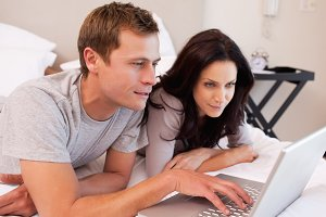 Couple using notebook together in the bedroom