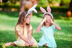 Two little girls wearing bunny ears on Easter outdoors