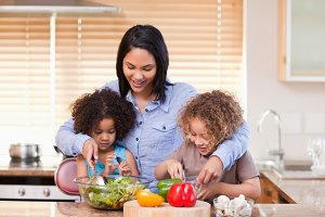 Mother and daughters preparing salad in the kitchen together