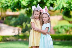 Girls wearing bunny ears on Easter day outdoors. Kids enjoy easter holiday