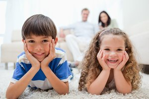 Happy kids lying on the carpet with parents behind them