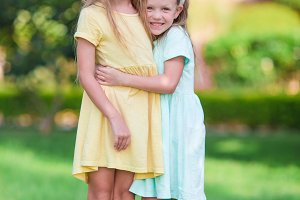 Two adorable little sisters wearing bunny ears on Easter day outdoors