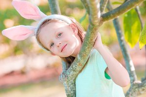 Adorable little girl wearing bunny ears on Easter at spring day