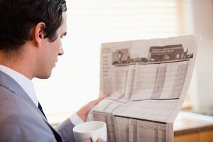 Side view of businessman reading newspaper