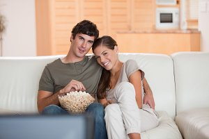 Couple with bowl of popcorn watching a movie on the sofa