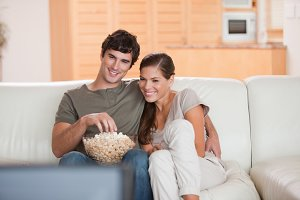 Couple with popcorn on the sofa watching a movie