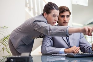 Businesswoman explaining computer program to colleague