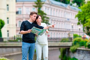 Young tourist couple traveling on holidays in Europe. Caucasian family with city map in search of attractions
