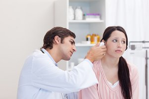 Male doctor examining his patients ear