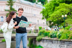 Couple traveling on their honeymoon in Europe. Caucasian family with city map in search of attractions