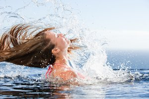Beautiful woman raising her head out of the water