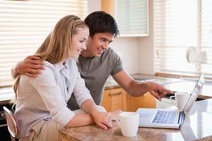 Couple having coffee while using a laptop