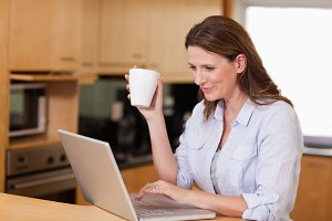 Woman drinking tea while on laptop