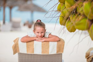 Adorable girl on lounger at tropical exotic beach under big coconuts