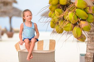 Little adorable girl near coconut on white tropical beach