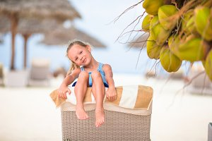 Little cute girl near coconut tree on white exotic beach