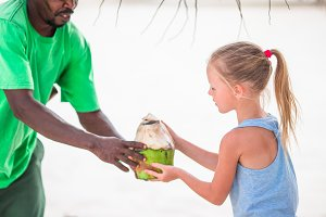 Little girl take the big coconut to drink the milk on bech vacation