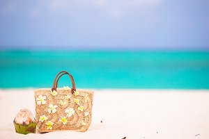 Beach bag with frangipani flowers and coconut on white beach. Closeup beach accessories.