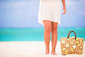 Closeup beautiful bag with frangipani flowers and sunglasses on white beach in female hands